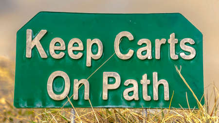 Panorama frame Close up view of a green and white sign that reads Keep Carts On Path. The signage is placed on a grass covered terrain beside a road.