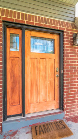 Vertical frame Home with brick and wood wall sections and glass paned front door and sidelight. A doormat and green garden hose can be seen by the doorstep. Standard-Bild - 129445438