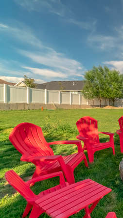 Vertical frame Red outdoor chairs and picnic table with bench around a circular stone fire pit. A playground can also be seen at this spacious backyard.