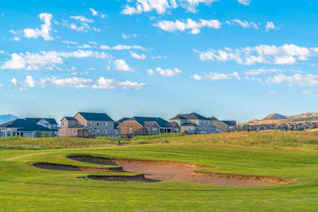 Golf course and houses with distant mountain and blue sky view on a sunny day Stock Photo