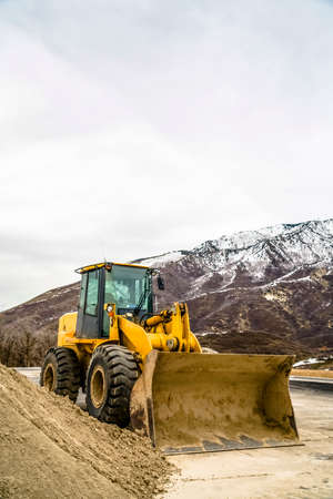 Front of a yellow bulldozer against snowy mountain and cloudy sky in winter. The dirty construction machinery is parked next to a mound of soil.