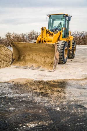 Focus on a yellow bulldozer with dirty bucket and wheels at a construction area. Leafless trees and cloudy blue sky can be seen in the background. Stock fotó