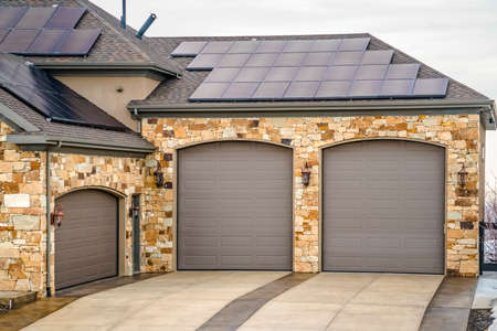 Home exterior with beautiful stone wall and solar panels on the roof. The driveway leads to the arched garage doors flanked by lanterns.