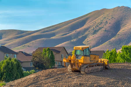 Yellow bulldozer on a construction site overlooking homes mountain and sky. The crawler has a metal blade used to push soil and other materials.