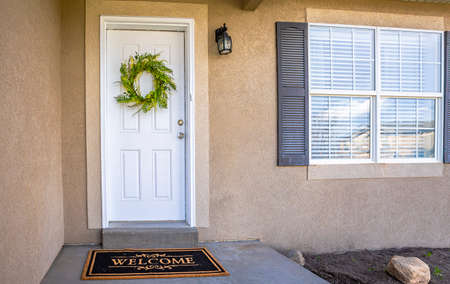 Puerta de entrada blanca con corona de hojas verdes y felpudo en la fachada de una casa. Junto a la puerta hay una ventana brillante con persianas y contraventanas. Foto de archivo