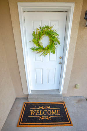 Green wreath hanging on the white front door of a home with a Welcome doormat. The house has a light brown concrete exterior wall.