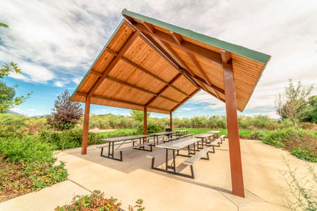 Sunny day at a park with view of tables and benches under a picnic pavilion. Lush foliage, blue sky, and puffy clouds can be seen in the background. Foto de archivo