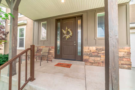 Porch and front door of a home with wood and stone brick wall sections. The door is decorated with a floral wreath and flanked by sidelights and windows.