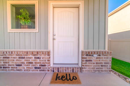 Front door and porch of home with hello mat