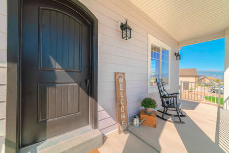 Front porch and door of traditional suburban home. The front porch and door of a traditional suburban home with a rocking chair and welcome sign.
