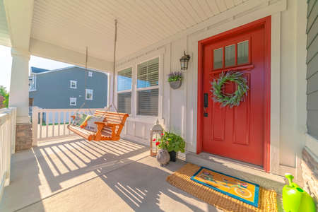 Front porch of modern home with swinging chair. The front porch of a modern home with a wreath on the door and a swinging chair.