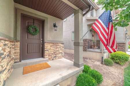Front door of suburban home with American flag