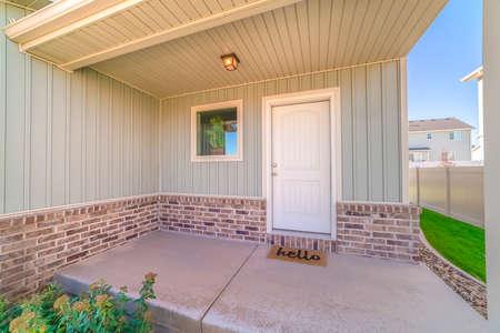 Haustür und Veranda des Hauses mit Willkommensmatte