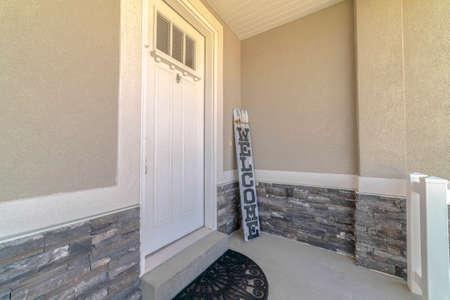 Haustür und Veranda des Hauses mit Willkommensschild