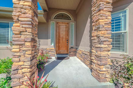 Front porch and door of house with stone pillars