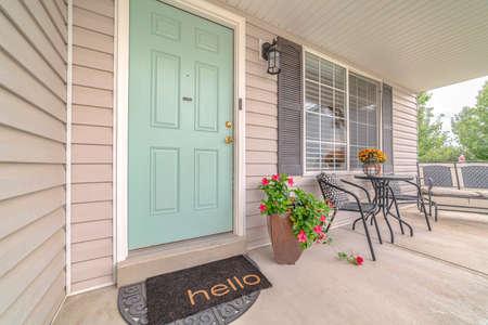 Puerta de entrada de casa suburbana con alfombra de bienvenida