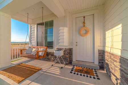 Front porch of modern home with swinging chair Archivio Fotografico