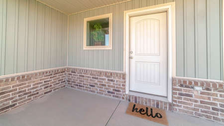 Panorama frame Front door and veranda of home with welcome mat. The front door and veranda of a modern home with a hello welcome mat.