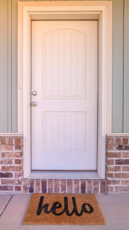 Vertical Front door and porch of home with hello mat. The front door and porch of a modern home with a hello welcome mat.