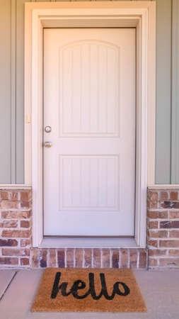 Vertikale Haustür und Veranda des Hauses mit Hallo-Matte. Die Haustür und die Veranda eines modernen Hauses mit einer Hallo-Willkommensmatte.