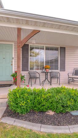 Vertikale vordere Veranda des modernen Hauses und des Landschaftsgartens. Die vordere Veranda und die Tür eines modernen Hauses mit einem grünen, angelegten Garten. Standard-Bild