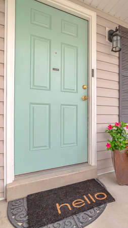 Vertical Front door of suburban home with welcome mat. The front door and porch of a suburban home with a hello welcome mat. Standard-Bild
