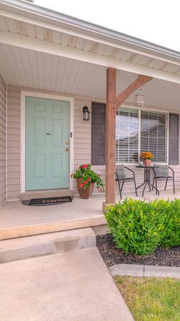 Vertikale Veranda des modernen Hauses mit Landschaftsgarten. Die Veranda und die Tür eines modernen Hauses mit einem grünen, angelegten Garten. Standard-Bild