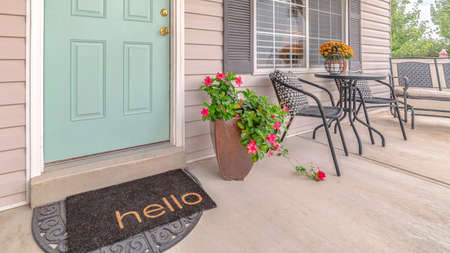 Panorama frame Front door of suburban home with welcome mat. The front door and porch of a suburban home with a hello welcome mat.