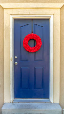 Vertical Bright red wreath on the blue front door of a home with outdoor wall lamp. A green garden hose is rolled beside the concrete doorstep.