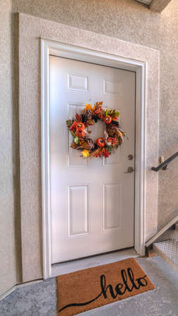 Vertical Apartment front door with welcome mat and wreath. The front door of an apartment door with a welcome mate and wreath from the exterior stairwell. Standard-Bild