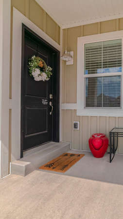 Vertical frame Front porch and door of traditional suburban home. The front porch and door of a traditional suburban home with a wreath and outdoor furniture. Archivio Fotografico