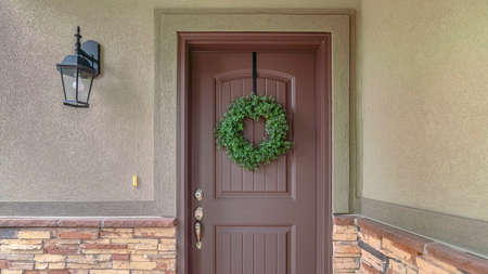 Panorama frame Front door of suburban home with green wreath. The front door and porch of a suburban home with a green wreath. Standard-Bild