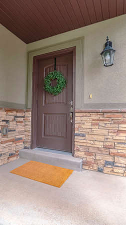 Vertical Entrance door to a house with feature stone wall. Entrance door to a house with feature stone wall surround and doormat below a wall lantern Imagens