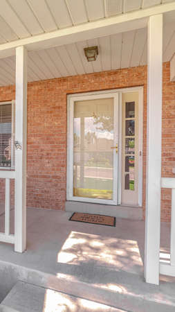 Vertical Front porch and door of traditional brick home. The front porch and door of a traditional suburban brick home. Standard-Bild