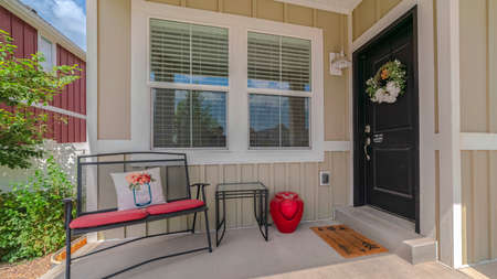 Panorama Front porch and door of traditional suburban home. The front porch and door of a traditional suburban home with a wreath and outdoor furniture.