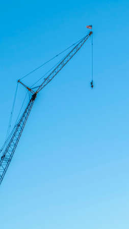 Vertical frame Construction crane for lifting and lowering materials isolated against blue sky Stock Photo