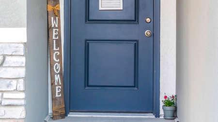Panoramarahmen Blaue Haustür eines Hauses mit Kranzwillkommensschild und Topfblume. Nahaufnahme des Eingangs eines Hauses mit Beton- und Steinmauer. Standard-Bild
