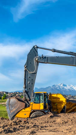 Vertical frame Excavator with metal arm and bucket and continuous tracks at a construction site. Towering mountain under blue sky can be seen in the distance.