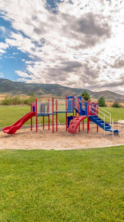 Vertical Fun childrens playground with amazing view of cloudy blue sky and mountain. Picnic pavilion and outdoor benches are also available at this park.