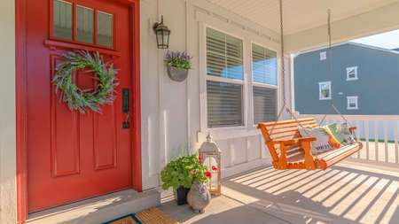 Panorama frame Front porch of modern home with swinging chair. The front porch of a modern home with a wreath on the door and a swinging chair.