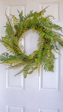 Vertical frame Close up of a simple fern wreath hanging on the white wood front door of a home