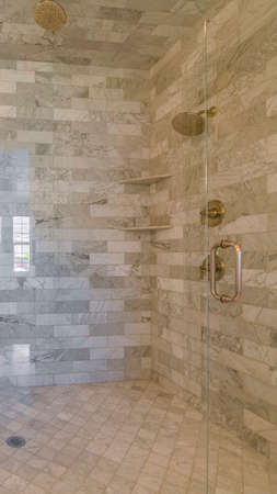 Vertical frame Interior of contemporary shower with stone tiles. The interior of a stylish, contemporary shower with stone tiles and glass shower screen.