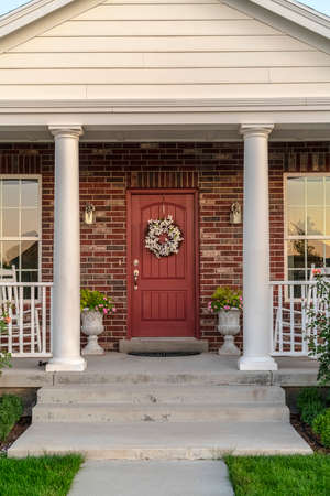 Front door to a house flanked by two pillars. Front door to a face brick house flanked by two pillars and windows with a dried wreath hanging on the wood Foto de archivo