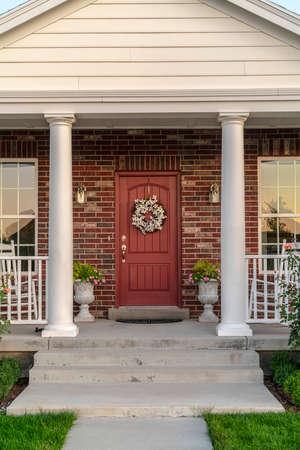 Porte d'entrée d'une maison flanquée de deux piliers. Porte d'entrée d'une maison en briques flanquée de deux piliers et de fenêtres avec une couronne séchée accrochée au bois Banque d'images
