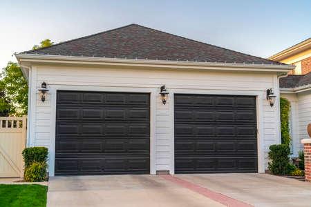 Unidad de garaje doble adosada a una casa suburbana. Unidad de garaje doble adjunta a una casa suburbana en una vista de la calle cercana con puertas cerradas