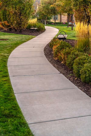 Paved walkway through a landscaped garden day. Paved walkway through a landscaped garden or park with shrubs and neat green lawns leading to a distant building behind trees