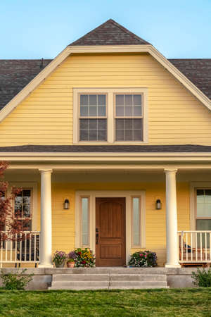Traditional timber clad front house facade near sunset. Traditional double storey timber clad front house facade with yellow walls and a covered front porch leading to a wooden door