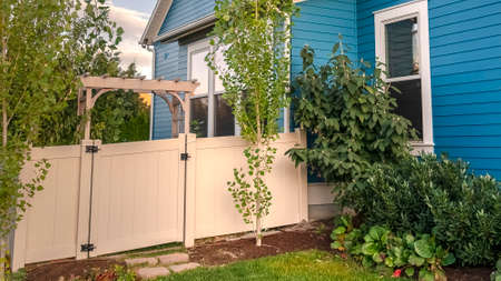 Panorama frame Blue timber clad house with neat fenced garden. External facade of a colorful blue timber clad house with neat fenced garden with internal gate into a backyard Stock Photo