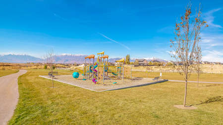 Panorama Colorful kids playground in a grassed urban park. Colorful kids playground in a grassed urban park in a residential neighbourhood with view to a distant mountain range