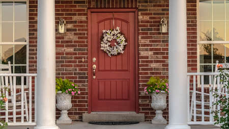 Panorama frame Front door to a house flanked by two pillars. Front door to a face brick house flanked by two pillars and windows with a dried wreath hanging on the wood